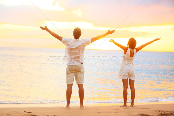 Happy cheering couple enjoying sunset at beach Stock photo © Maridav