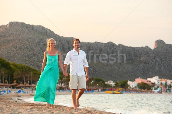 Romantic beach couple walking at sunset Stock photo © Maridav
