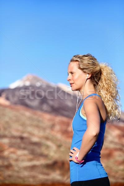 Running earphones - woman runner listening music Stock photo © Maridav