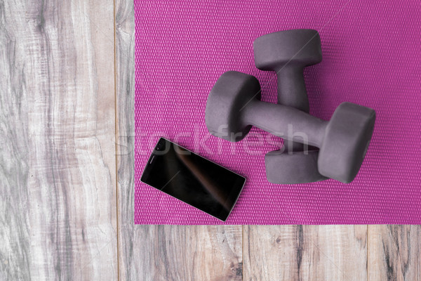 Fitness at home-weights yoga mat mobile phone app Stock photo © Maridav