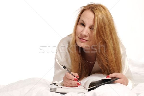 Woman writing in journal Stock photo © markhayes