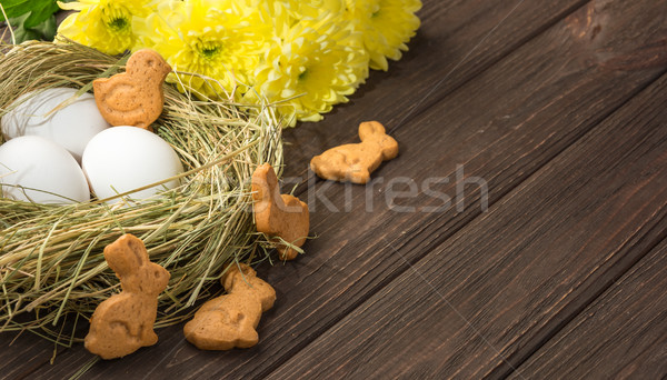 Easter eggs in a straw nest, Easter bunny cookies and yellow flo Stock photo © markova64el
