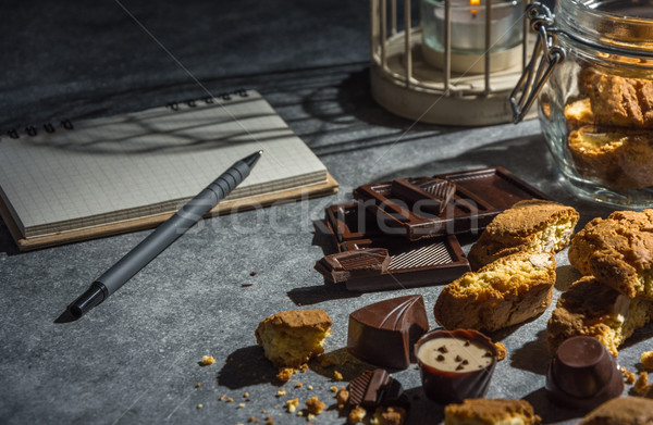 Almond cookies, chocolates and notebook in dark key. Stock photo © markova64el