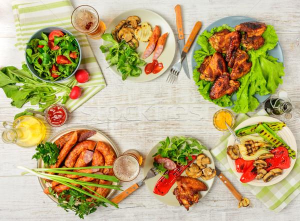 Ebédlőasztal választék étel sültcsirke szárnyak kolbászok Stock fotó © markova64el