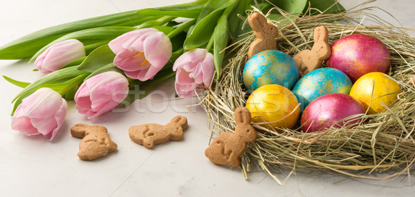 Easter eggs in a straw nest, Easter bunny cookies and  tulips on Stock photo © markova64el