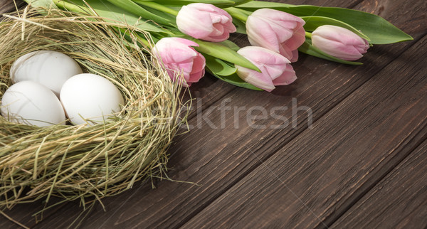 Easter eggs in a straw nest and  tulips  Stock photo © markova64el