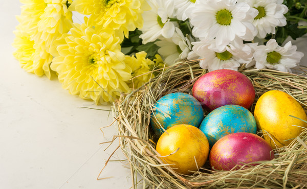 Easter eggs in a straw nest, Easter bunny cookies , and flowers  Stock photo © markova64el