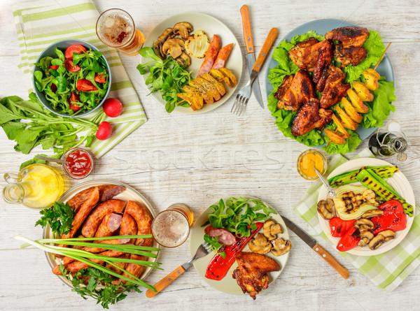 Mesa de jantar variedade comida frango assado asas salsichas Foto stock © markova64el