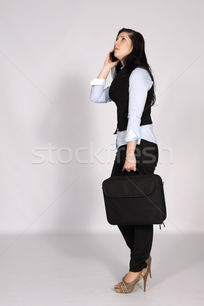 Mulher jovem chamada em pé laptop saco telefone Foto stock © maros_b