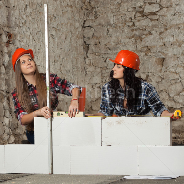 Two young long-haired woman built a new wall from blocks Stock photo © maros_b