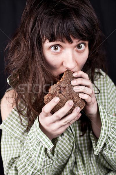 Bedelaar vrouw eten brood portret arme Stockfoto © marylooo