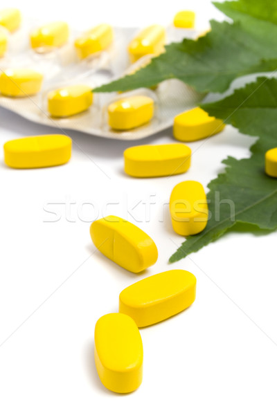 yellow vitamin pills and green leaves Stock photo © marylooo