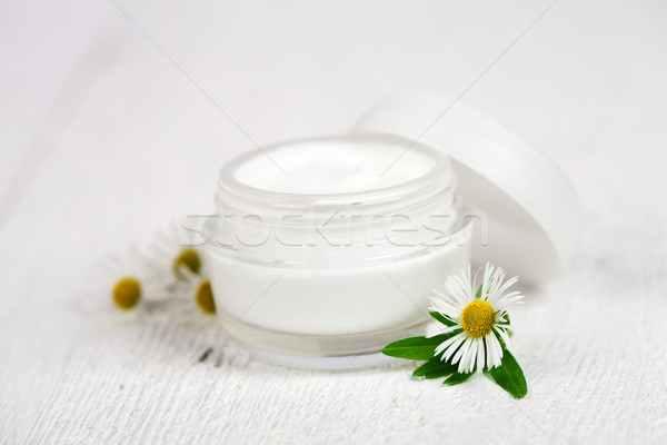 Stock photo: container with cream and camomiles