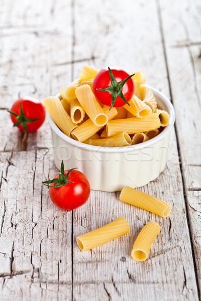 Stock photo: uncooked pasta and cherry tomatoes in a bowl