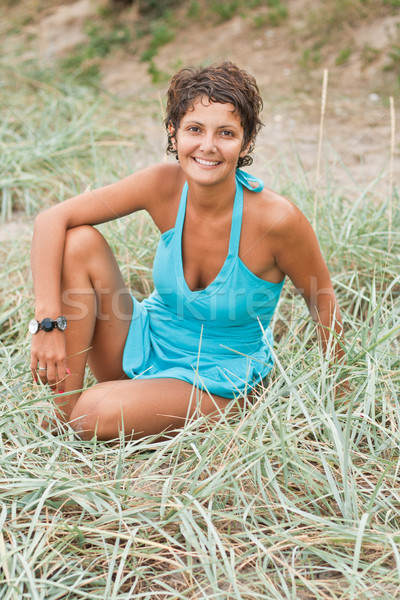 brunet woman in blue sitting in a grass Stock photo © marylooo