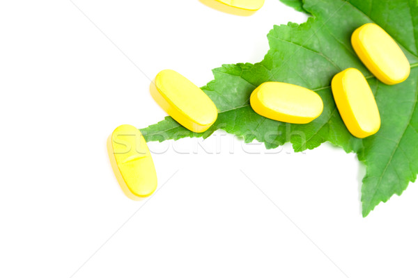 yellow vitamin pills over green leaf Stock photo © marylooo