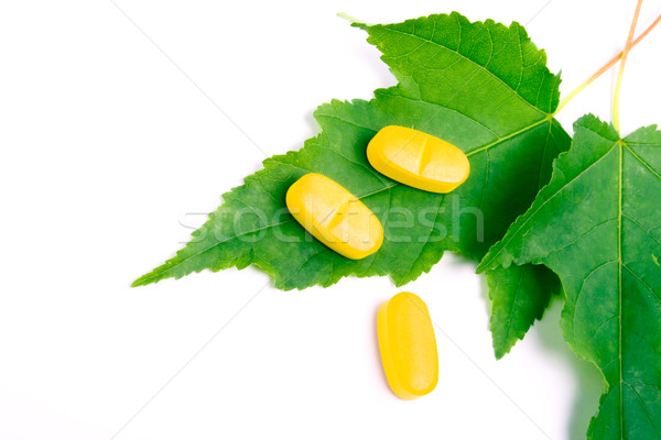 yellow vitamin pills over green leaves Stock photo © marylooo