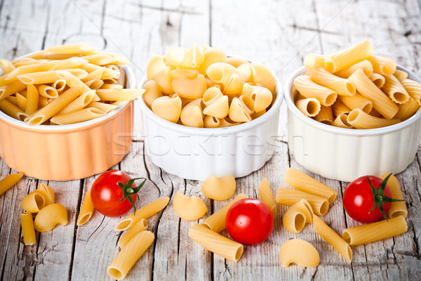 three bowls with uncooked pasta and cherry tomatoes Stock photo © marylooo