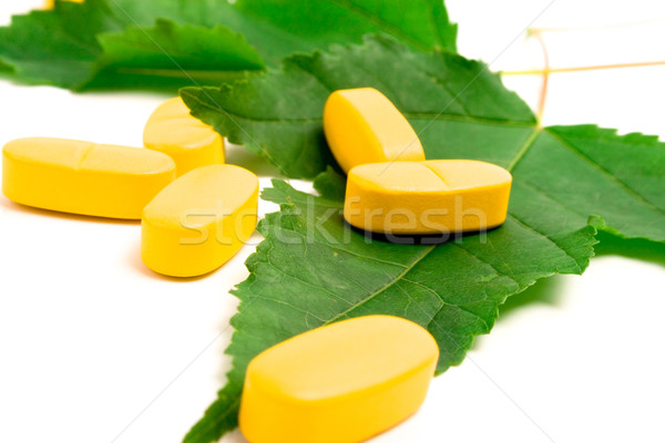 vitamin pills over green leaves Stock photo © marylooo