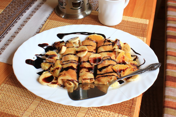 Pancakes stuffed with semolina, bananas and oranges drenched dark chocolate Stock photo © MarySan
