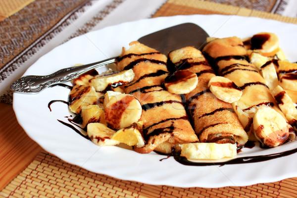 Pancakes stuffed with semolina, bananas and oranges drenched dark chocolate Stock photo © MarySan