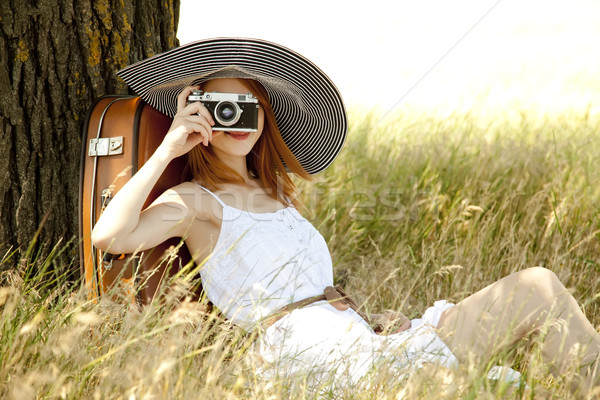 Stock photo: Redhead girl sitting near tree with vintage camera.