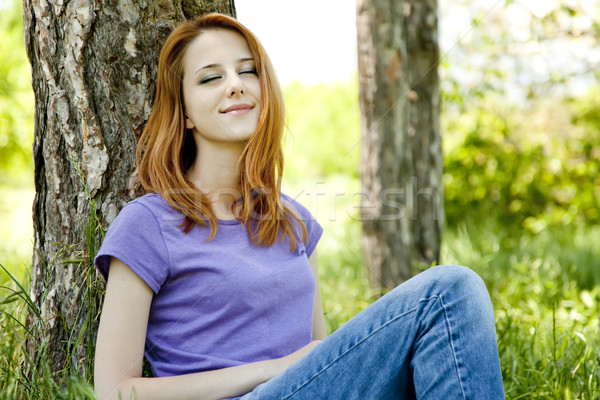 Beautiful red-haired girl sitting at green grass at park. Stock photo © Massonforstock