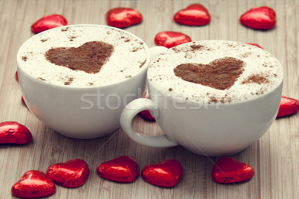 Two cup of coffee with heart symbol and candy around. Stock photo © Massonforstock