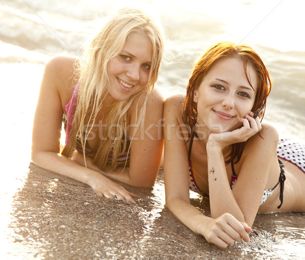 Two beautiful young girlfriends in bikini on the beach Stock photo © Massonforstock