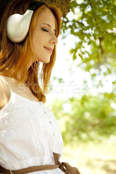 Stock photo: Beautiful redhead girl with headphones at garden.