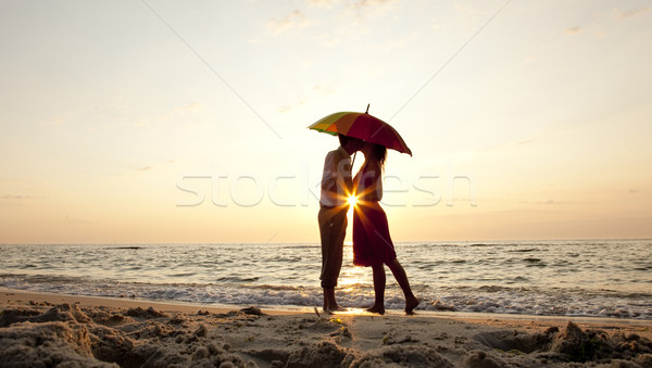 Casal beijando guarda-chuva praia pôr do sol água Foto stock © Massonforstock