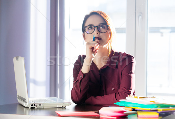 beautiful young woman sitting at the desk and thinking about som Stock photo © Massonforstock