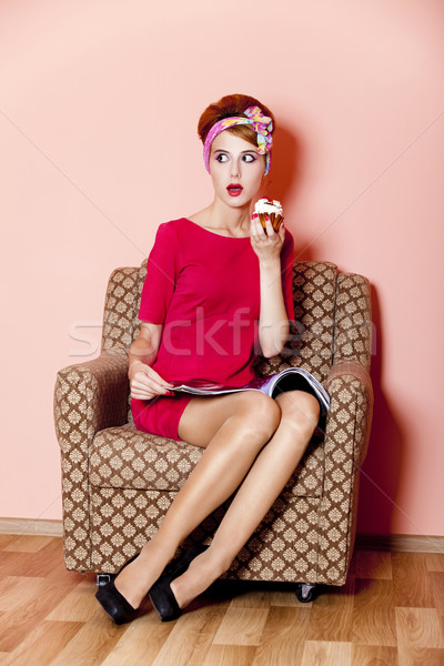 style girl in red dress sitting in armchair with cake and magazi stock photo volodymyr nikulin. Black Bedroom Furniture Sets. Home Design Ideas