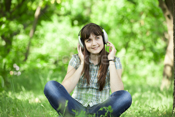 Young fashion girl with headphones at green spring grass. Stock photo © Massonforstock