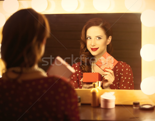 photo of beautiful young woman holding her gift near the window  Stock photo © Massonforstock