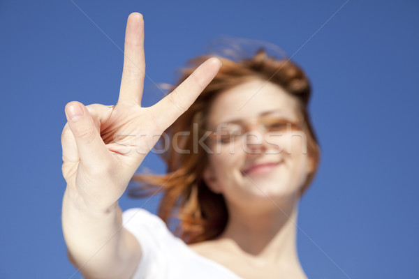 Portrait of red-haired girl in white which show hand V symbol. Stock photo © Massonforstock