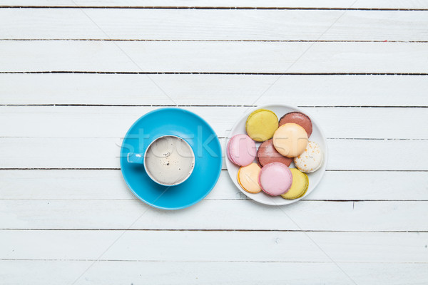 Stock photo: photo of blue cup of coffee and plate full of macaroons on the w