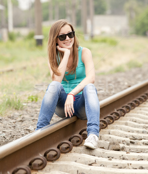 Young girl in glasses sitting at railway. Stock photo © Massonforstock