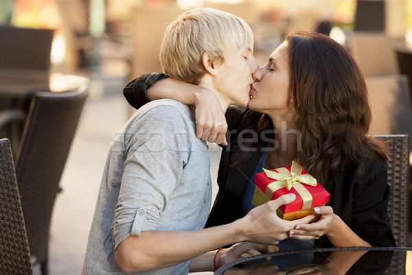 The young man gives a gift to a young girl in the cafe and they  Stock photo © Massonforstock