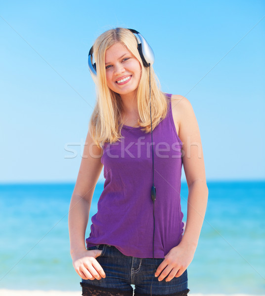 Portrait of blonde girl with headphone on the beach. Stock photo © Massonforstock