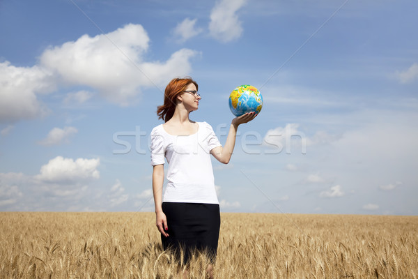 Young Businesswomen in white keeping globe in hand at wheat fiel Stock photo © Massonforstock
