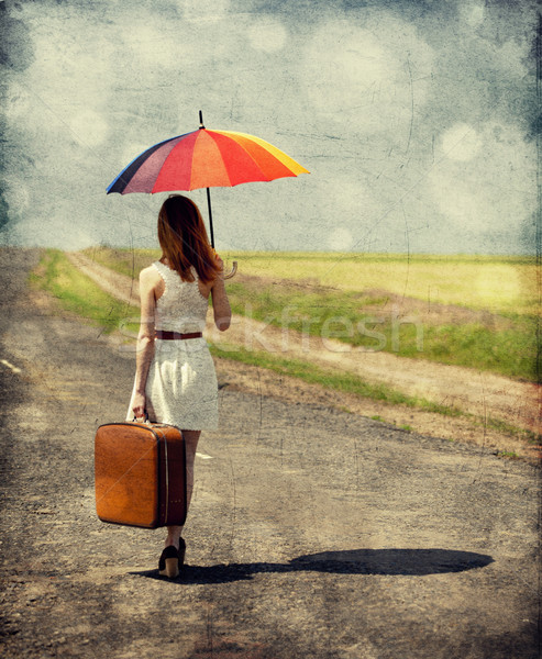 Young fashion girl with umbrella and suitcase at spring outdoor. Stock photo © Massonforstock
