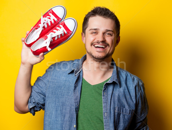 young smiling guy in shirt with red gumshoes  Stock photo © Massonforstock