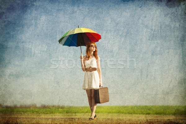 Redhead enchantress with umbrella and suitcase at spring country Stock photo © Massonforstock