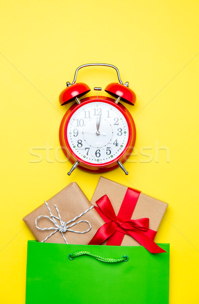 cute gifts in beautiful green shopping bag and alarm clock on wo Stock photo © Massonforstock