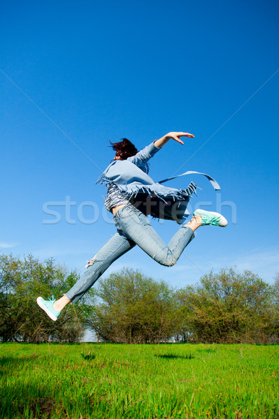 beautiful young woman jumping on the field in front of trees bac Stock photo © Massonforstock