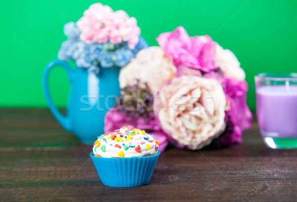 photo of tasty glazed donut near wonderful flowers in vase and c Stock photo © Massonforstock