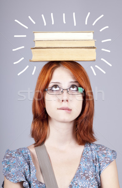 Red-haired girl keep books on her head. Studio shot. Stock photo © Massonforstock