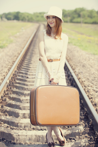 Stock photo: Young fashion girl with suitcase at railways.