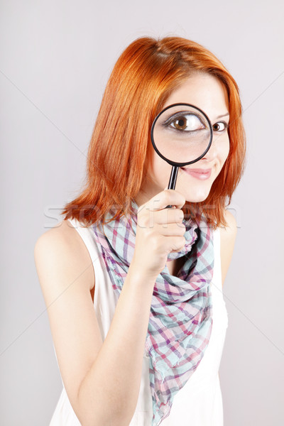 Beautiful red-haired girl with loupe zooming her eye. Stock photo © Massonforstock